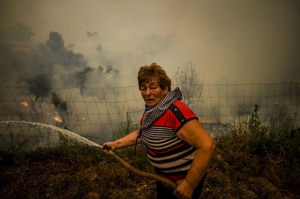 Aldeão usa mangueira de água para apagar chamas durante incêndio na aldeia de Roda, no centro de Portugal, em 21 de julho de 2019