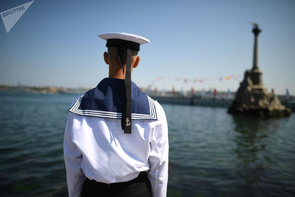 Marinheiro no cais perto do monumento aos Navios Afundados em Sevastopol, na Rússia