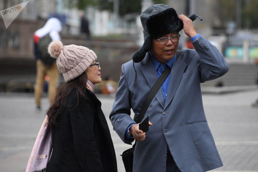 Turistas estrangeiros se agasalham com gorros na praça Manezhnaya durante o tempo frio em Moscou