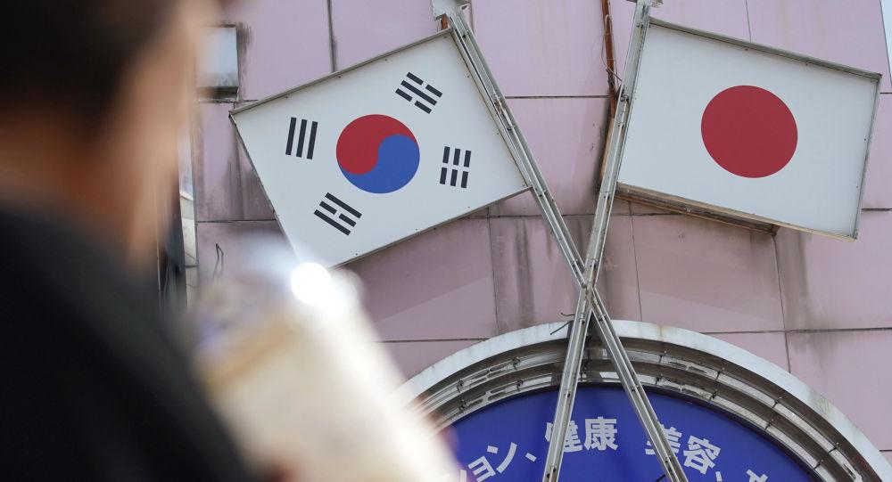 Mulher caminha enfrente anúncio com as bandeiras sul-coreana e japonesa