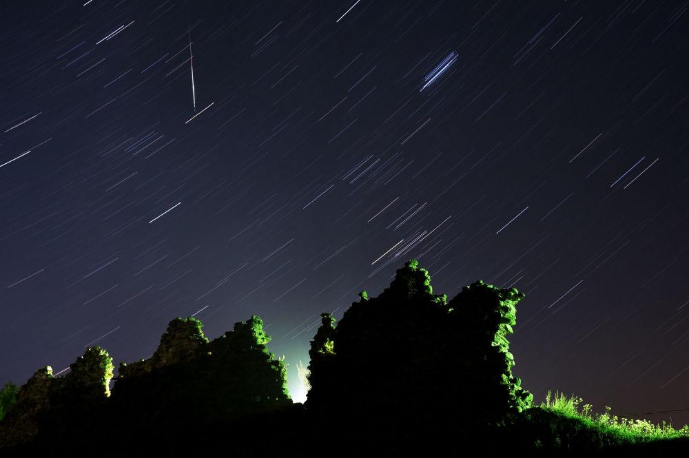 Chuva de meteoros Perseidas sobre as ruínas do castelo medieval na povoação de Kreva, na Bielorrússia