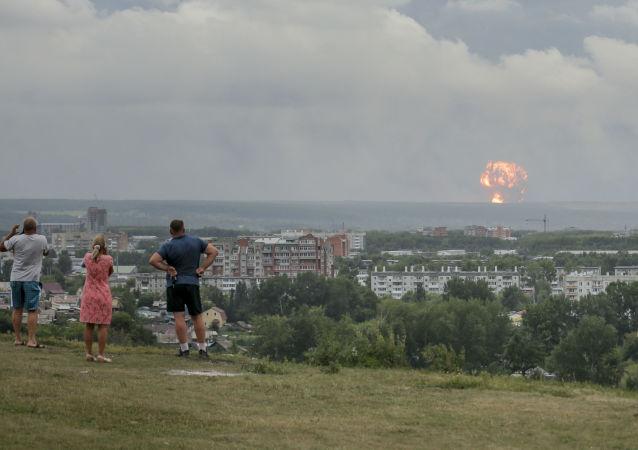 Pessoas assistem e fotografam explosões em um depósito de armamento militar próximo da cidade de Achinsk, na região de Krasnoyarsk, na Rússia. Autoridades russas disseram que explosões deixaram feridos no local, além de forçarem uma evacuação. A foto foi tirada em 5 de agosto de 2019.
