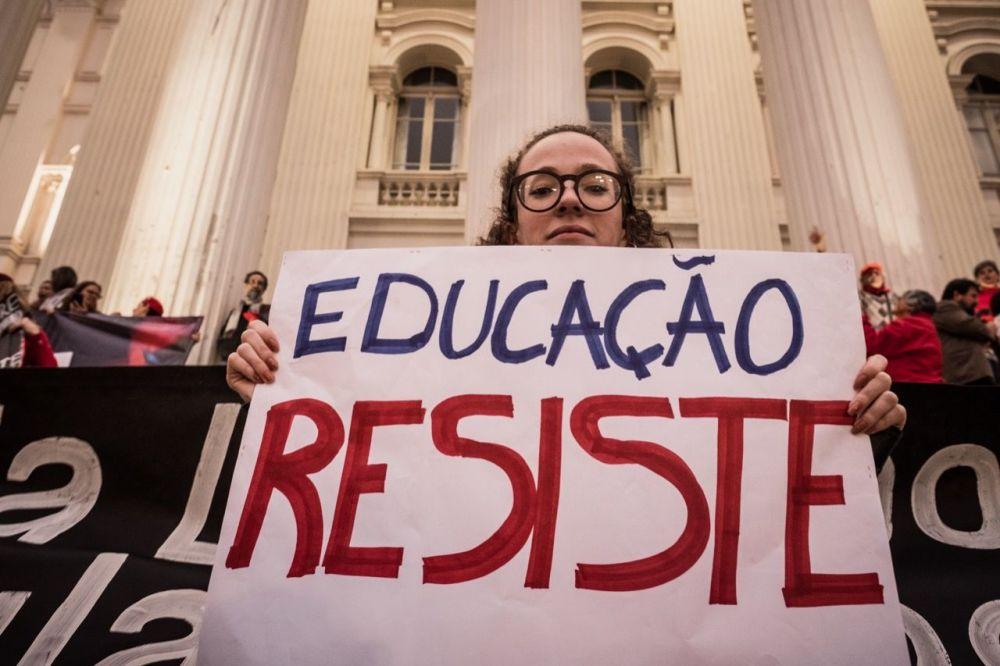 Manifestante segura cartaz durante protesto em defesa da educação em Curitiba