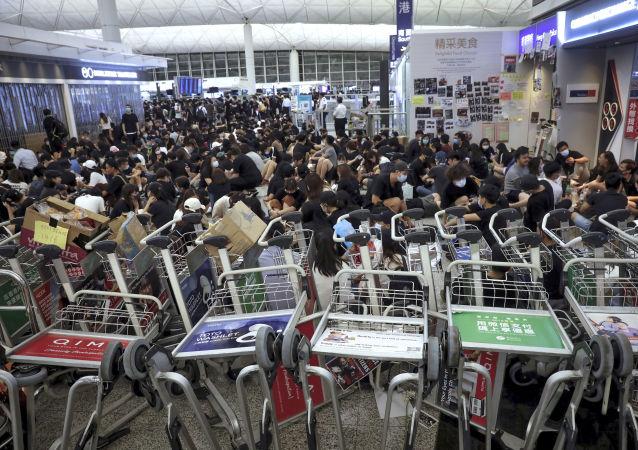 Manifestantes usam carrinhos de bagagem para bloquear a passagem para os portões de embarque durante uma demonstração no aeroporto de Hong Kong