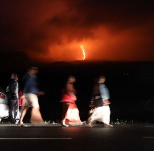 Pessoas passeiam enquanto a lava desce da cratera do vulcão Piton de la Fournaise na parte oriental da ilha de Reunião, no oceano Índico, 13 de agosto de 2019
