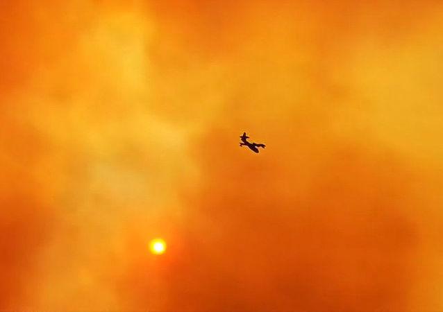 Avião atravessa céu laranja devido às chamas causadas por incêndios na ilha grega de Euboea