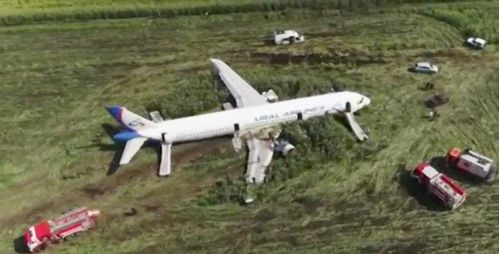 Avião visto de cima após aterrissagem, cercado por serviços de emergência