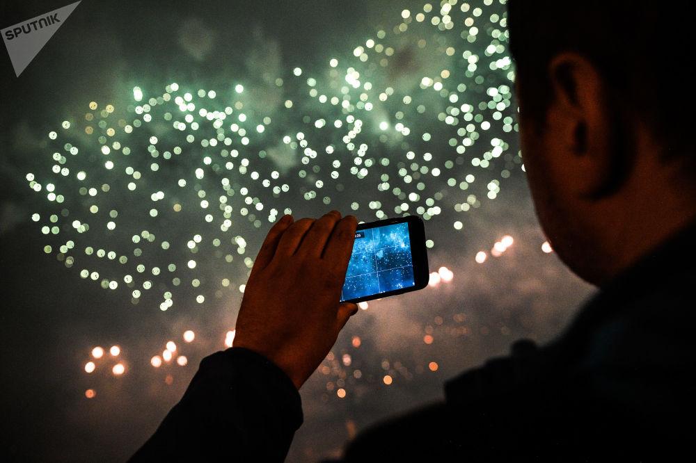 Visitante faz vídeo no Festival Internacional de Fogos de Artifício Rostec no Parque Brateyevskiy, em Moscou, 17 de agosto de 2019