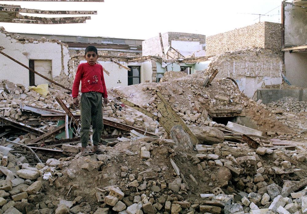 Menino iraniano nas ruínas da sua antiga casa destruída em 23 de janeiro em um ataque aéreo iraquiano em Ahvaz, em 25 de janeiro de 1987