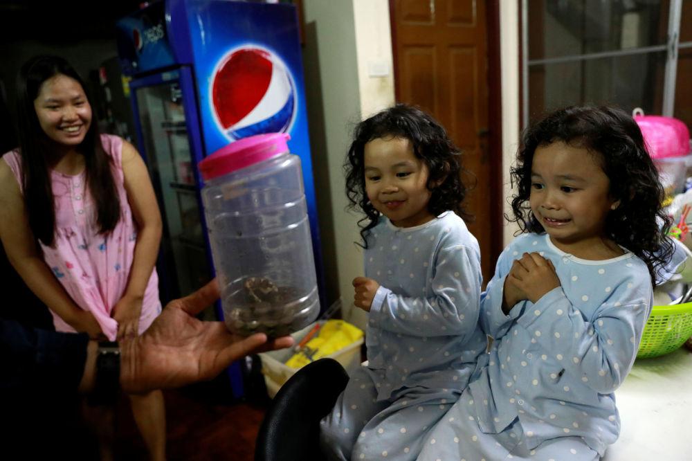 Reação de garotas enquanto bombeiro Pinyo Pukpinyo mostra uma pequena píton