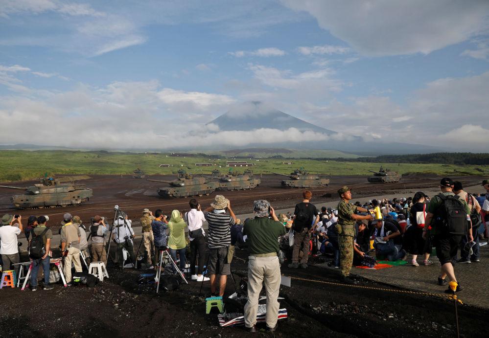 Tanques e veículos blindados em frente do monte Fuji vistos dos lugares dos espectadores