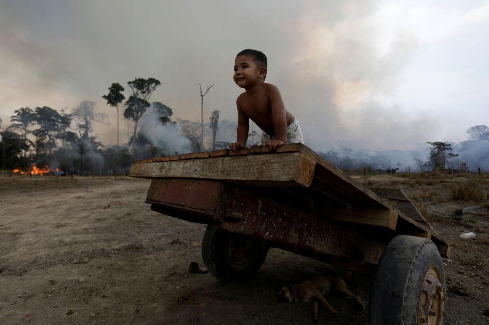 Criança brinca no meio de incêndios florestais na Amazônia