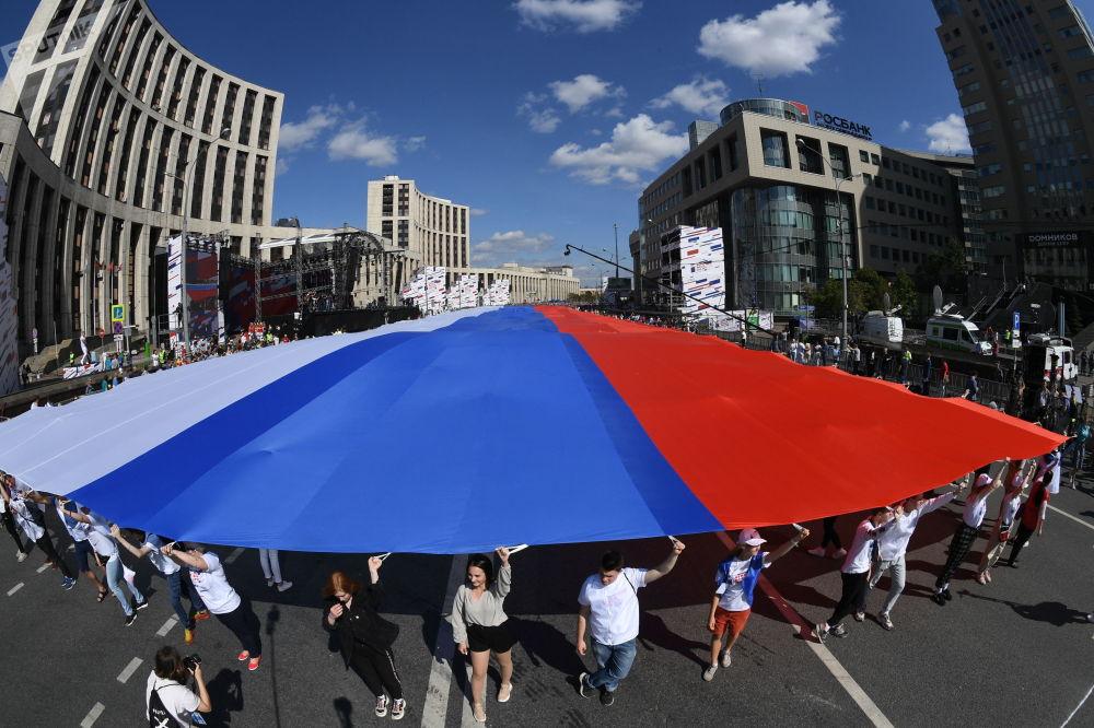 Participantes da festa do Dia da Bandeira Nacional da Rússia com uma enorme bandeira russa em Moscou
