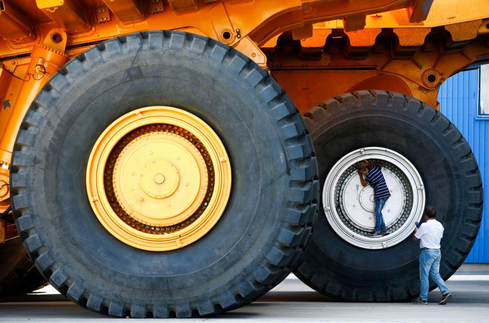 Pessoas tiram fotos perto das rodas de um caminhão basculante BelAZ na fábrica de automóveis de Zhodino, na Bielorrússia