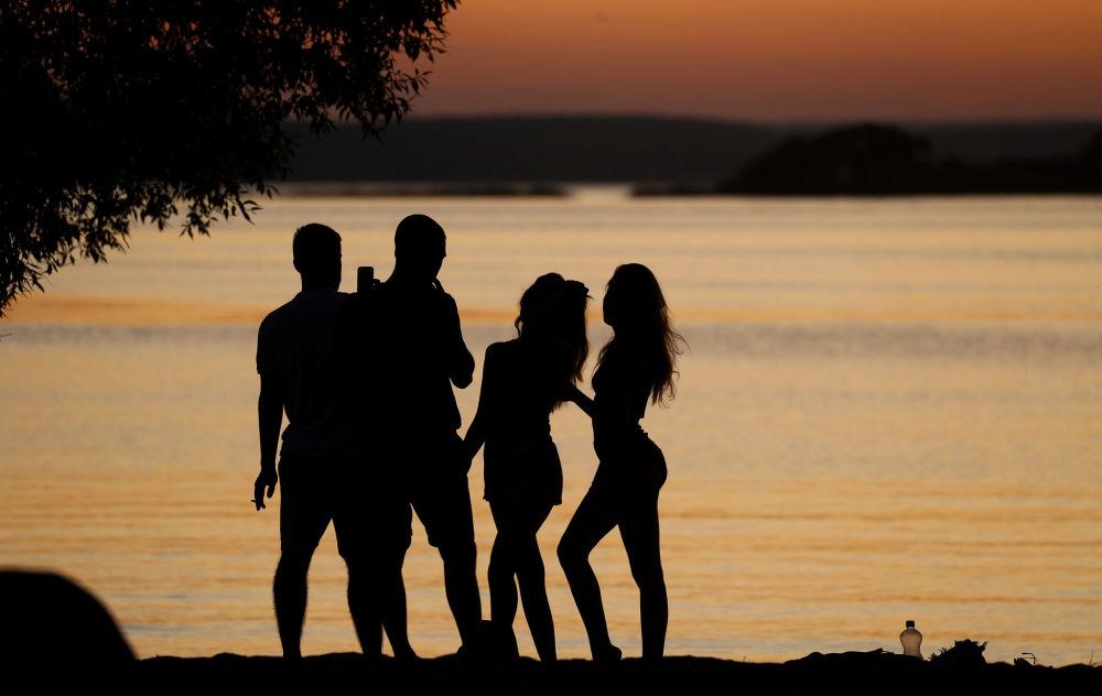 Pessoas observam pôr do sol perto do lago na cidade de Minsk, capital da Bielorrússia
