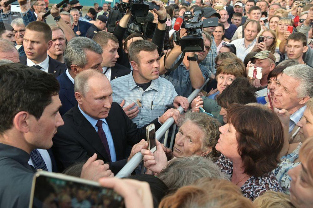 Presidente russo, Vladimir Putin, conversando com moradores da cidade russa de Tulun após ter visitado uma escola local