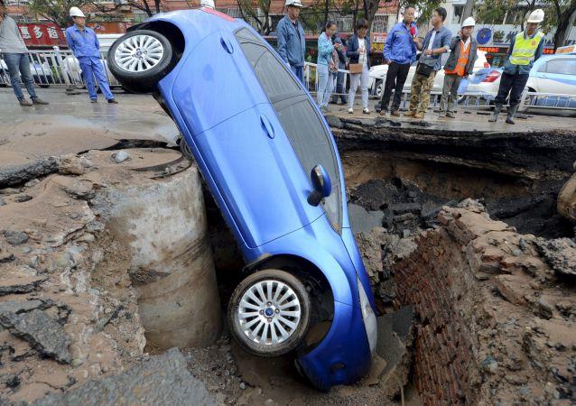 Carro é engolido por cratera aberta no meio da rua na província de Gansu, na China (imagem referencial)
