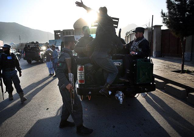 Policiais afegãos deixam local de ataque suicida  próximo ao Ministério da Defesa do Afeganistão, em Cabul, em 27 de fevereiro de 2016.