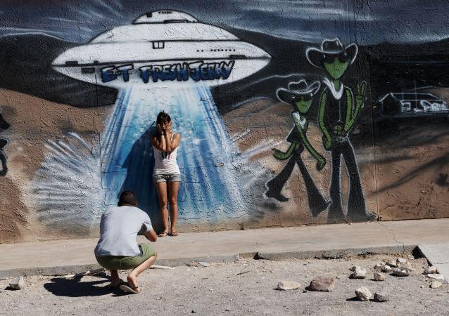 Jovem tira foto na frente de parede com grafite de OVNI em Hiko, Nevada, EUA, 20 de setembro de 2019