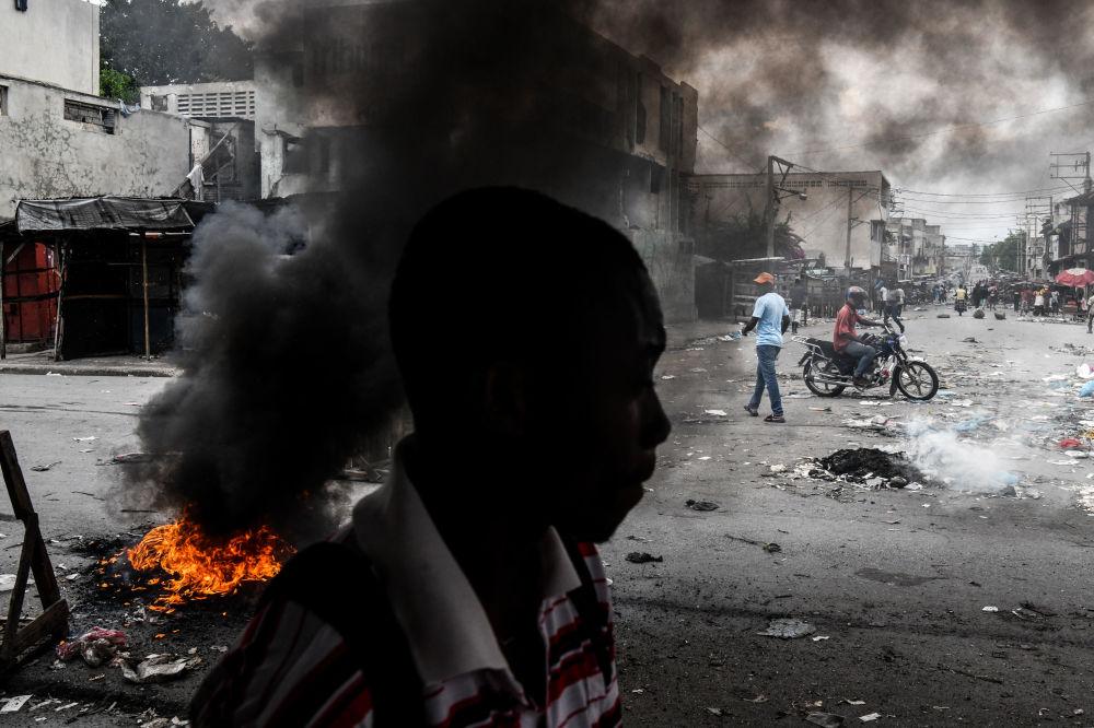 Homem passando em frente a pneus queimados por manifestantes durante protestos contra o presidente haitiano Jovenel Moise em Porto Príncipe, capital do Haiti