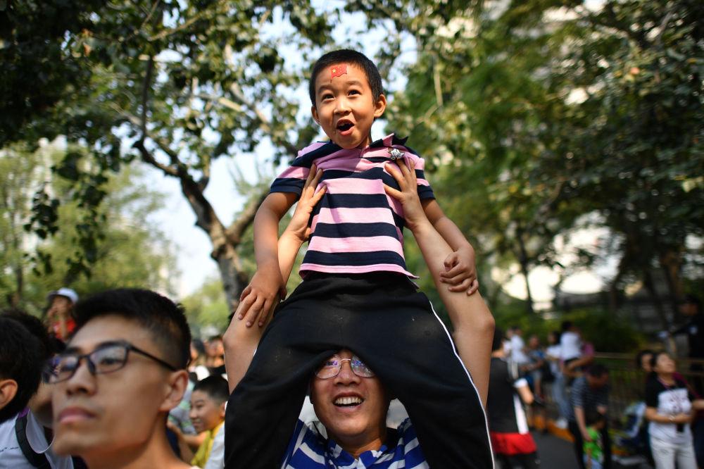 Pessoas observando o desfile militar dedicado ao 70º aniversário da fundação da República Popular da China, em Pequim