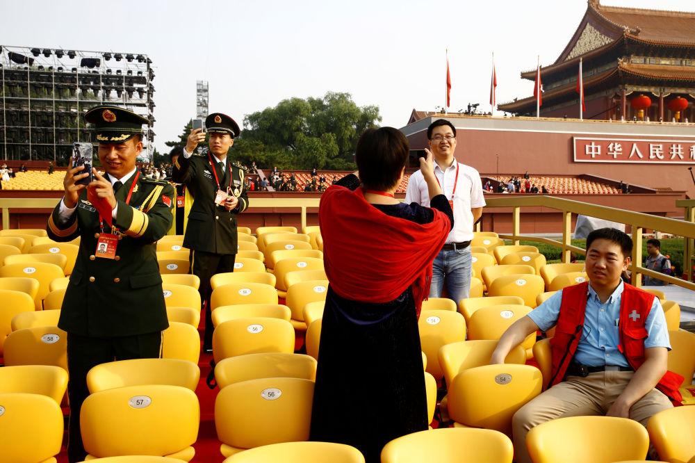 Delegados antes do início do desfile militar marcando o 70º aniversário da fundação da República Popular da China, em Pequim
