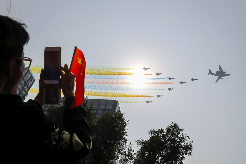 Homem tirando fotos dos aviões durante o desfile militar marcando o 70º aniversário da fundação da República Popular da China, em Pequim