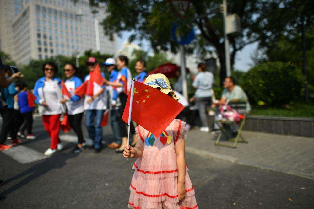 Menina com a bandeira da China durante o desfile militar marcando o 70º aniversário da fundação da República Popular da China, em Pequim