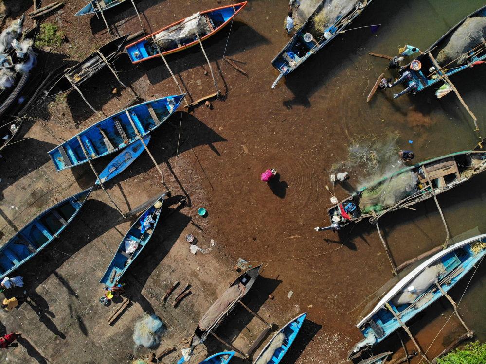 Vendedores compram peixe em um porto de pesca na aldeia de Agonda, na Índia