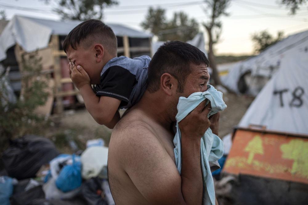 Homem com criança durante confrontos perto do campo de refugiados de Moria, na ilha grega de Lesbos