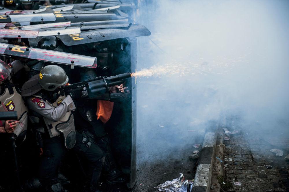 Policial usa gás lacrimogêneo durante confronto com manifestantes em Bandung, Indonésia