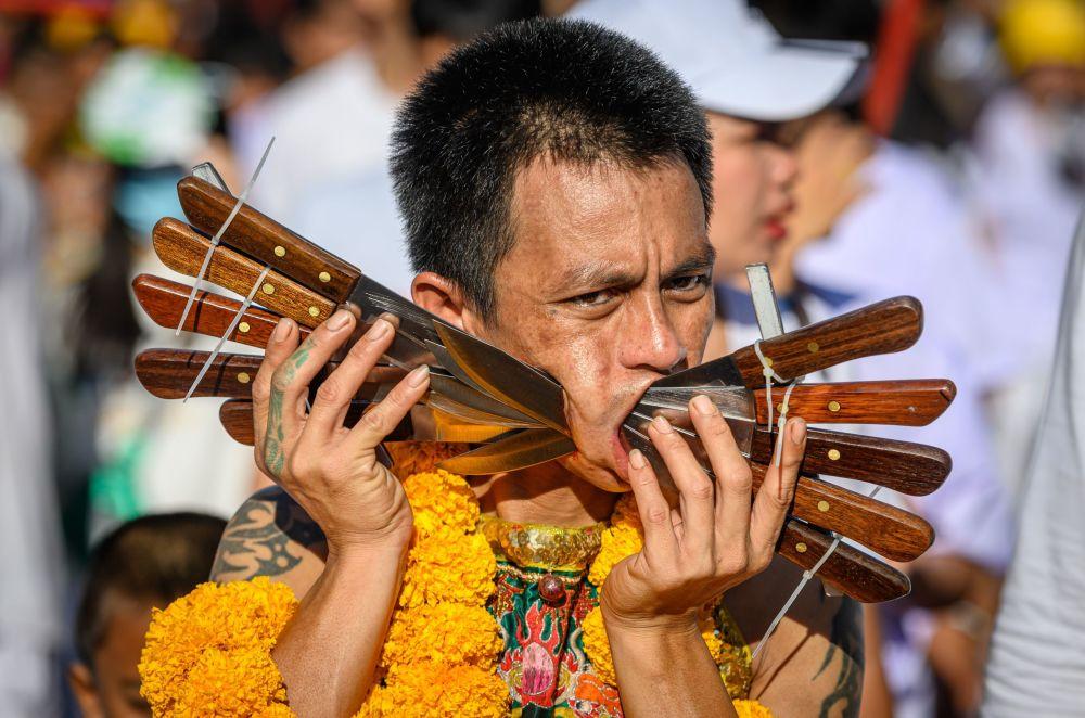 Participante de festival vegetariano anual, com bochechas perfuradas por faca, em Phuket, na Tailândia, em 3 de outubro de 2019