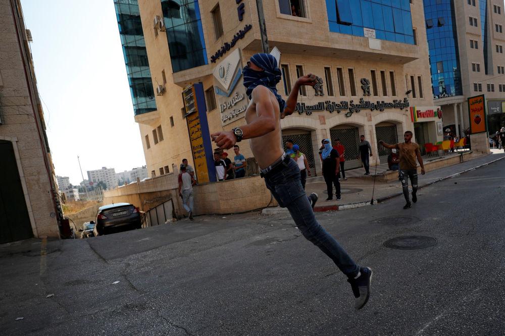 Manifestante atira pedras em militares israelenses durante ato de solidariedade com os prisioneiros palestinos nas prisões de Israel