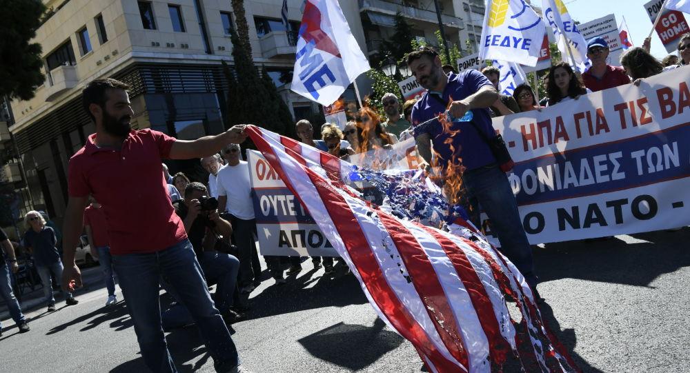 Um dos grupos de manifestantes se reuniu em frente à embaixada dos EUA em Atenas, onde queimaram uma bandeira americana