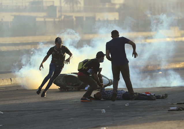 Manifestantes correm para ajudar um homem ferido durante protesto em 5 de outubro de 2019 contra o governo em Bagdá, no Iraque. Protestos começaram na terça-feira em diversas cidades do país contra corrupção e desemprego.