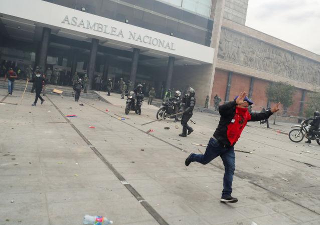 Manifestante entra em confronto com a polícia em frente a sede do Parlamento do Equador