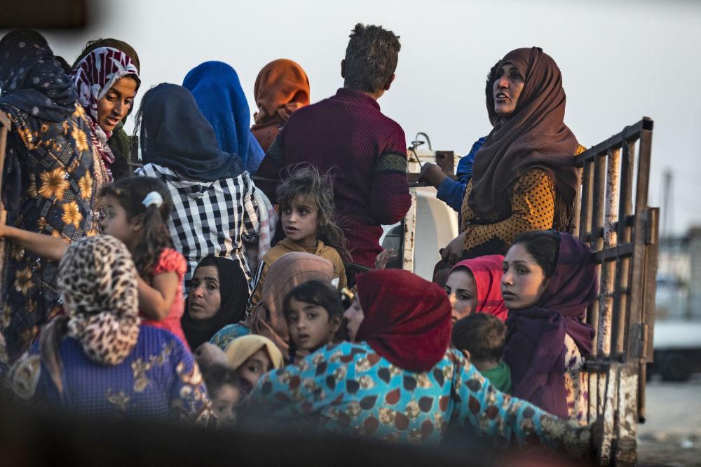 Civis sírios árabes e curdos fugindo em meio ao bombardeio da cidade fronteiriça de Ras al-Ain pela Turquia