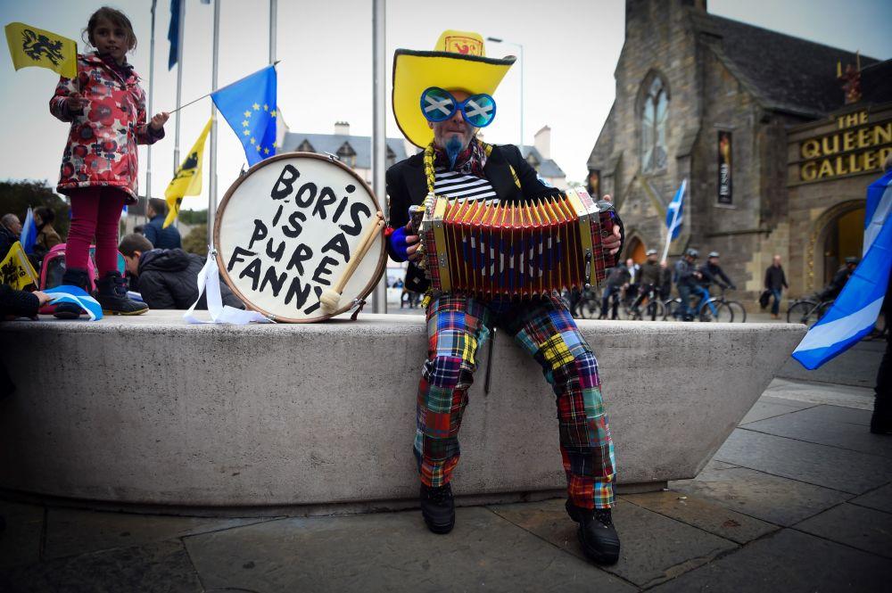 Manifestante tocando acordeão enquanto espera pelo início de marcha pela independência na Escócia