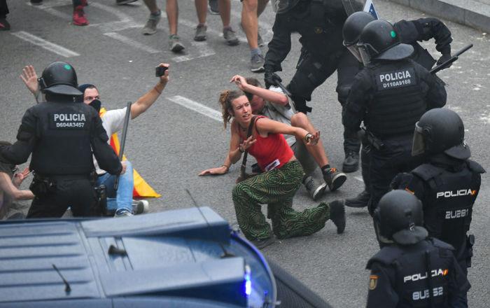Manifestantes colidem com policiais espanhóis fora do aeroporto El Prat, em Barcelona, em 14 de outubro de 2019, quando milhares de manifestantes furiosos saíram às ruas depois que a Suprema Corte da Espanha condenou nove líderes separatistas catalães a entre nove e 13 anos de prisão por sedição na sequência da fracassada tentativa de declaração de independência em 2017