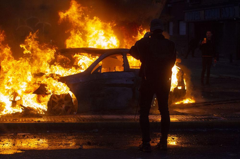 Chilenos observam carro queimado durante protestos contra o governo no Chile