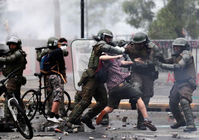 Tropa de choque tenta deter manifestante durante protestos em Santiago do Chile