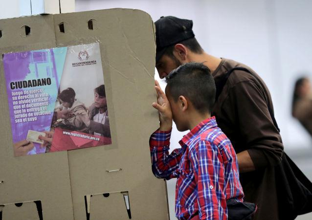 Um homem acompanhado por seu filho deposita seu voto em Bogotá nas eleições locais da Colômbia, em 27 de outubro de 2019.