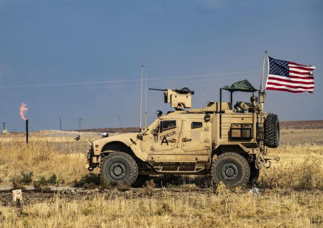 Veículo blindado norte-americano passa perto de campo de extração de petróleo, ao patrulhar a cidade síria de Al-Qaryatayn, em 31 de outubro de 2019