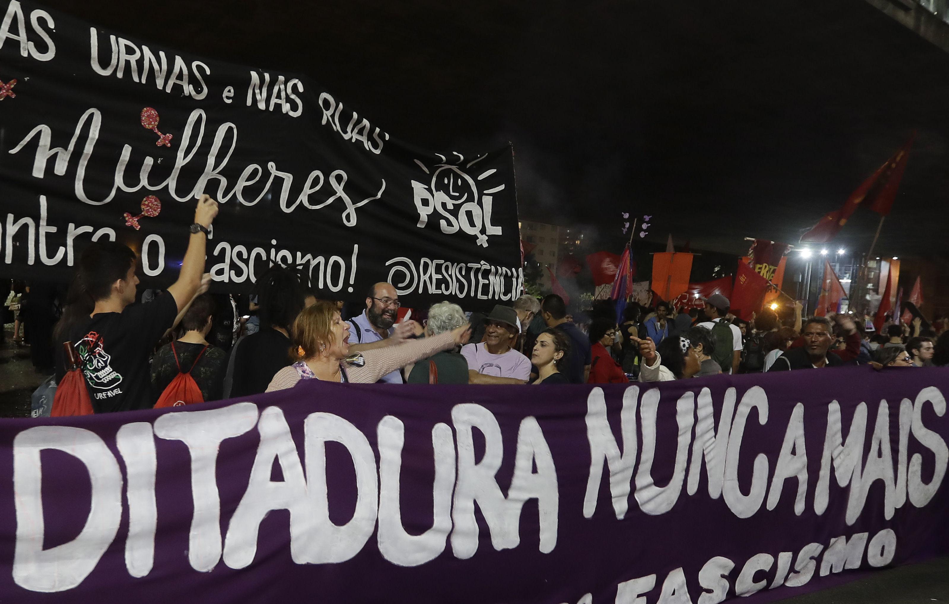 Manifestantes protestam contra o governo Bolsonaro com uma faixa escrita Ditadura Nunca Mais em São Paulo