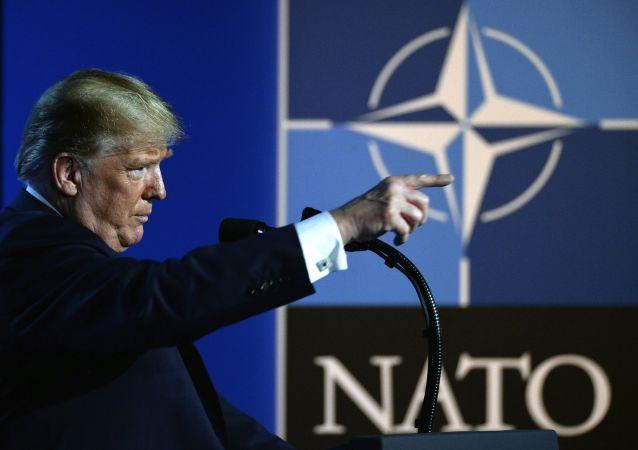 Presidente dos EUA, Donald Trump em frente à logo da OTAN.