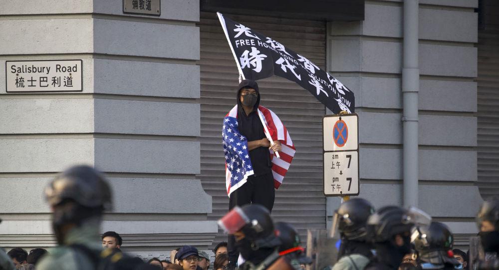 Manifestante em Hong Kong envolto na bandeira dos EUA, em 1º de dezembro de 2019