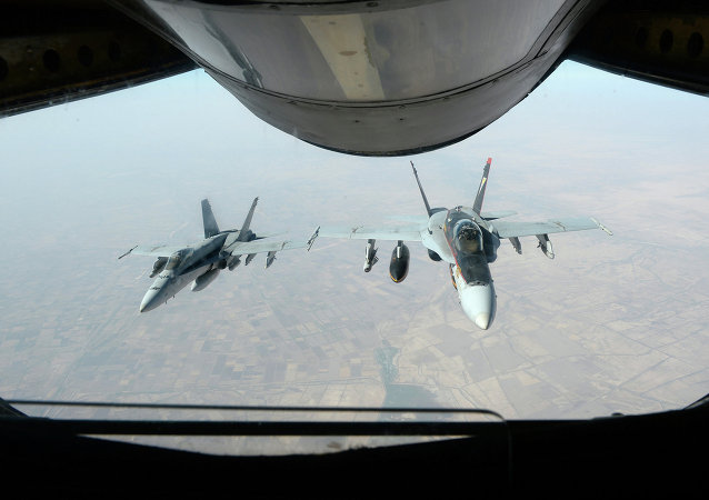 Two U.S. Navy F/A-18E Super Hornet aircraft fly after receiving fuel from an Air Force KC-135 Stratotanker aircraft over Iraq Oct. 4, 2014
