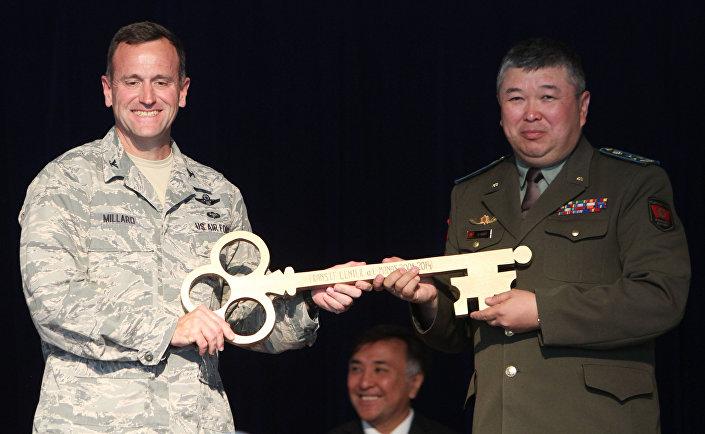 Comandante da base militar Manas, John Millard (esquerda) passa a chave simbólica ao vice-ministro da Defesa do Quirguistão, Zamir Suerkulov