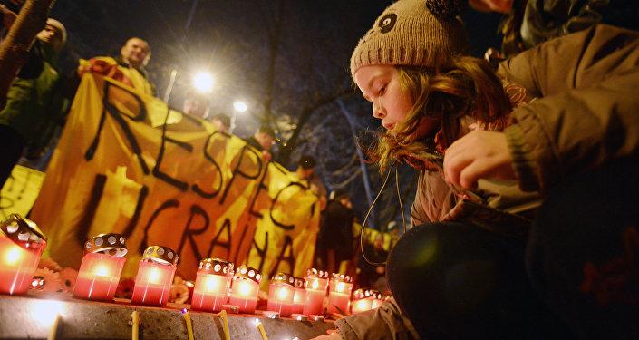 Em frente à embaixada da Ucrânia em Bucareste, romenos acendem velas em sinal de respeito às vítimas dos violentos protestos da Praça Maidan em fevereiro do ano passado, os quais resultaram na subida ao poder do governo nacionalista ucraniano pró-ocidental de Pyotr Poroshenko.