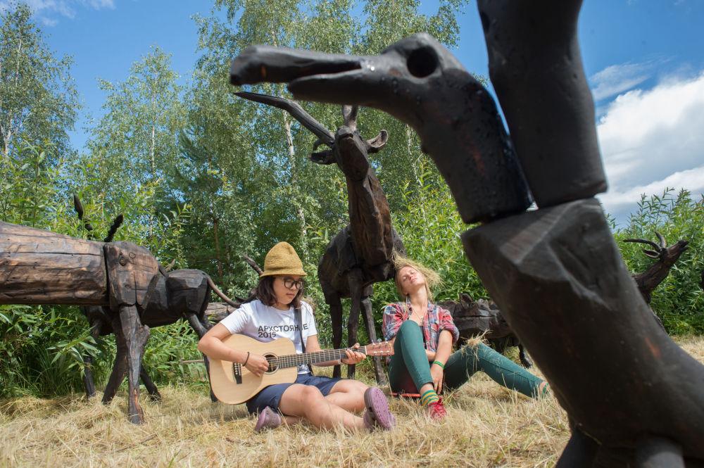 Visitantes descansam perto das esculturas de madeira